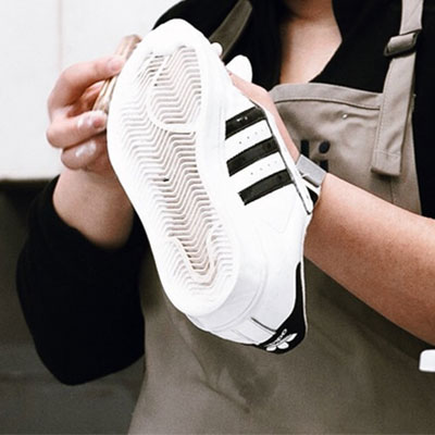 picture of a technician cleaning a sneaker